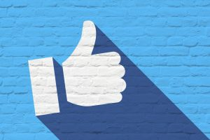 Facebook to eliminate ad set budget - blue background with white thumbs up