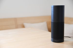 a black Amazon Alexa on a wood table